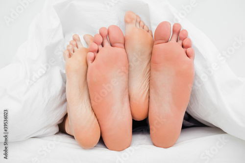 Two pairs of feet crossed over each other in bed