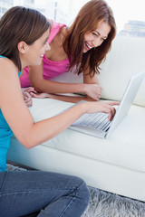 Smiling young women using a laptop on a white sofa