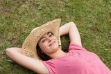 Young smiling woman lying on the grass with eyes closed