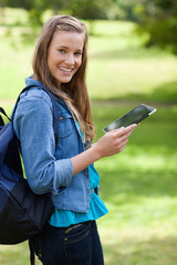 Smiling young adult using her tablet computer while carrying her backpack