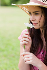 Young attractive woman smelling a flower while wearing a straw hat