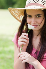 Young peaceful girl smelling a flower while standing in a park with a straw hat