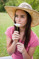 Young attractive girl smelling a flower in the countryside