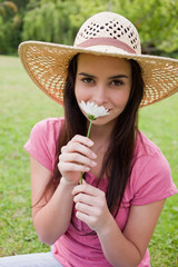 Young attractive woman wearing a hat in a park while smelling a flower