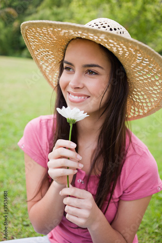 Smiling young woman wearing a hat in a park while smelling a flower