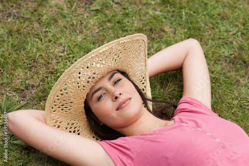 Young beautiful woman lying on the grass while wearing a hat
