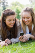 Smiling young girls looking at a mobile phone while lying in a park