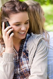 Young smiling girl talking on the phone while being accompanied by a friend