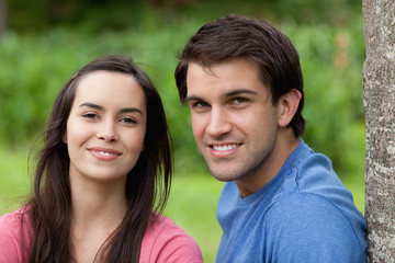 Young smiling couple standing side by side in the countryside
