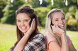 Young smiling women talking on the phone while standing back to back