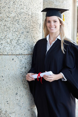 Young smiling graduating student holding her diploma