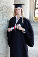 Young serious graduating student holding her diploma