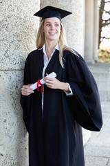 Smiling graduating student standing upright with her diploma