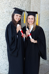 Two young smiling graduating students holding their diplomas