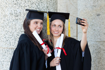 Young happy graduating students photographing themselves