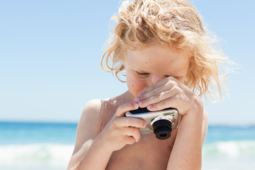 Boy looking at screen of a digital camera at the beach