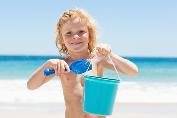 Boy with a bucket and shovel on the beach