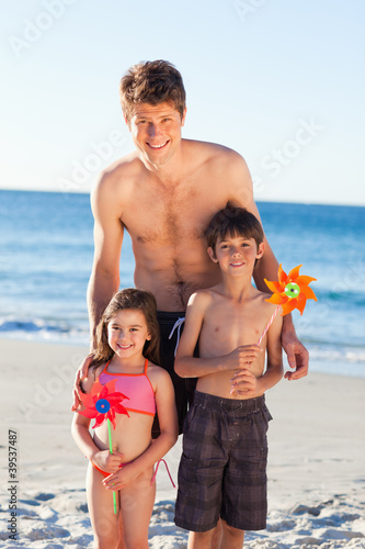 Smiling father on the beach together with his children
