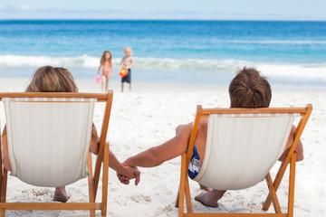 Parents watching their children walking at the beach