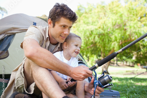 A smiling father shows his son how to fish