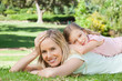 Mother with her hand on her head as her daughter rests on her mother's back