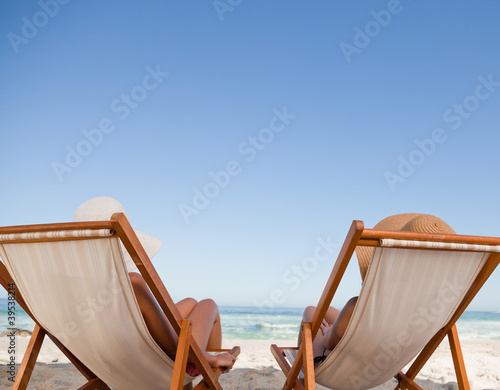 Attractive young women lying on deck chairs
