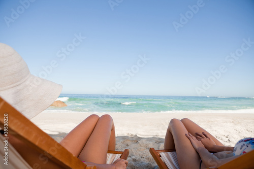 Young women tanning in the sun while lying on deck chairs