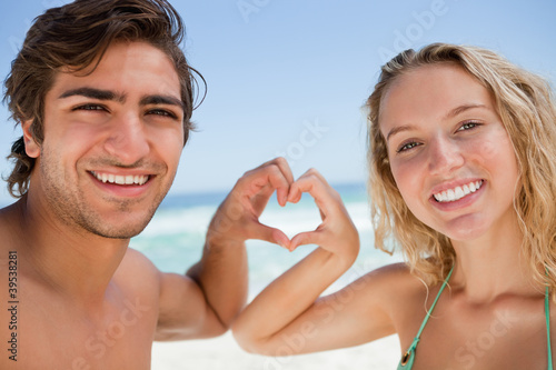 Attractive woman and her boyfriend joining their hands to make a heart shape