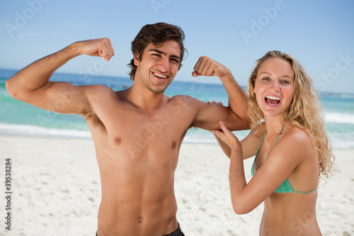 Young smiling woman touching her boyfriend's biceps