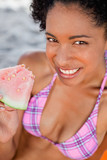 Young smiling woman holding a piece of watermelon while sitting on the beach