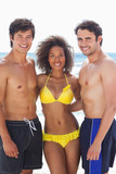 Woman wearing a bikini smiling as she holds her two friends