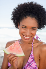 Young smiling woman sitting on the beach while holding a piece of watermelon