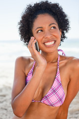 Young smiling woman talking on the phone while sitting on the beach
