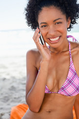 Young smiling woman looking at the camera while talking on the phone