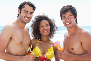 Three friends in swimsuits smiling while holding cocktails