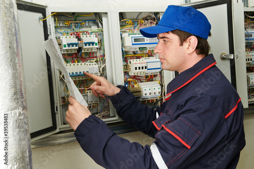 Electrician at work with draw plan