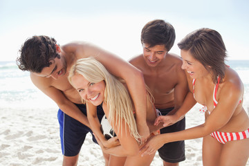Woman smiling she tussles with her friends for a football