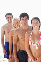 Woman in a bikini smiling happily as she stands in front of her three friends