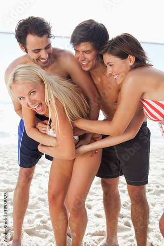 Four friends laughing as they tussle for a football