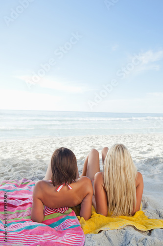Two women lying on their towels sunbathing at the beach