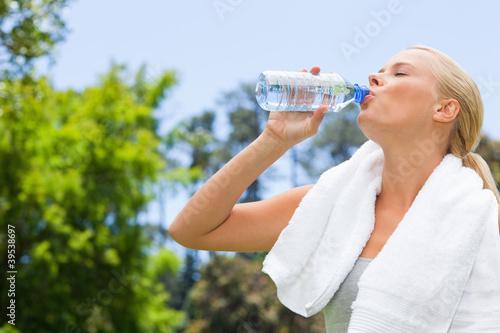Side view of sportswoman drinking water