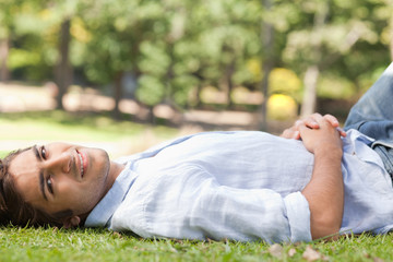 Side view of smiling man relaxing on the lawn
