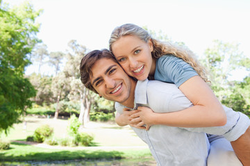 Smiling man carrying his girlfriend on his back