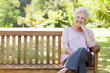 Woman smiling happily as she sits on a bench