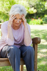 Woman with a worried expression sittting on a bench