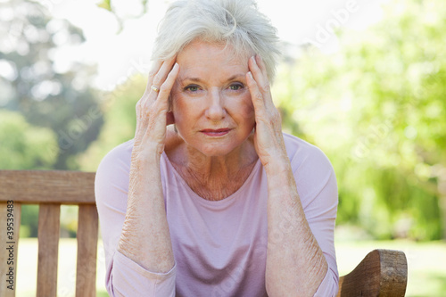 Woman looking ahead while holding her head