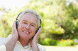 Man smiling as he uses headphones to listen to music