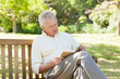 Man seriously reading a book as he sits on a bench