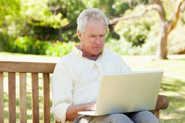 Man using a laptop while sitting on a bench