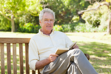 Man looking to his side while holding a book as he sits on a bench